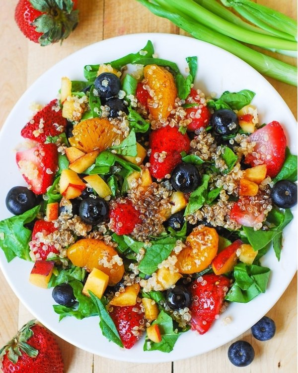 Quinoa Salat mit Spinat, Erdbeeren, Blaubeeren und Pfirsiche in…
